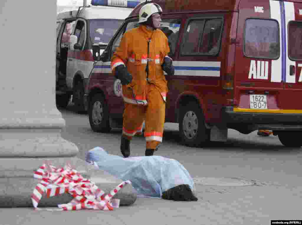 The body of a victim is seen on the ground near the entrance to the subway station.