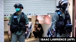 Hong Kongda polisiýa barlag operasiýasyny geçirýän mahaly, dükan satyjysy garaşýar. 28-nji iýun, 2020 ý.