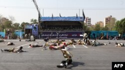 This picture taken on September 22, 2018 in the southwestern Iranian city of Ahvaz shows soldiers lying on the ground at the scene of an attack on a military parade.
