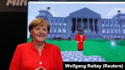 GERMANY -- German Chancellor Angela Merkel stands next to a screen depicting a Minecraft rendition of her and the Reichstag building during the opening of the world's largest computer games fair Gamescom in Cologne, Germany, August 22, 2017.