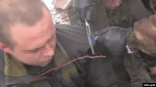Givi uses a knife to cut the chevrons from the jackets of the prisoners, before stuffing them into their mouths.