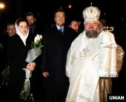 Тодішній прем'єр-міністр України Віктор Янукович з дружиною Людмилою та митрополит Донецький і Маріупольський Ілларіон (Роман Шукало) у кафедральному Свято-Преображенському соборі в Донецьку, 7 квітня 2007 року