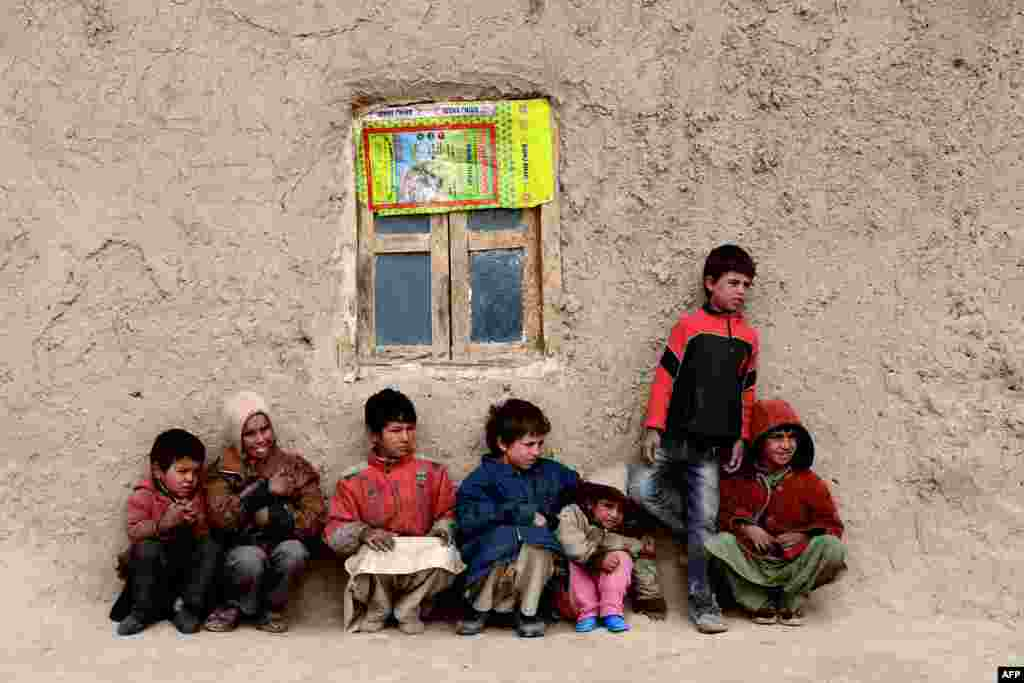 Afghan children sit near their home in Herat. (AFP/Aref Karimi)