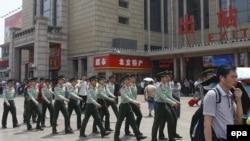 Сотрудники службы безопасности железнодорожного вокзала в Пекине усилили дежурство после инцидента в Урумчи. 23 мая 2014 года.