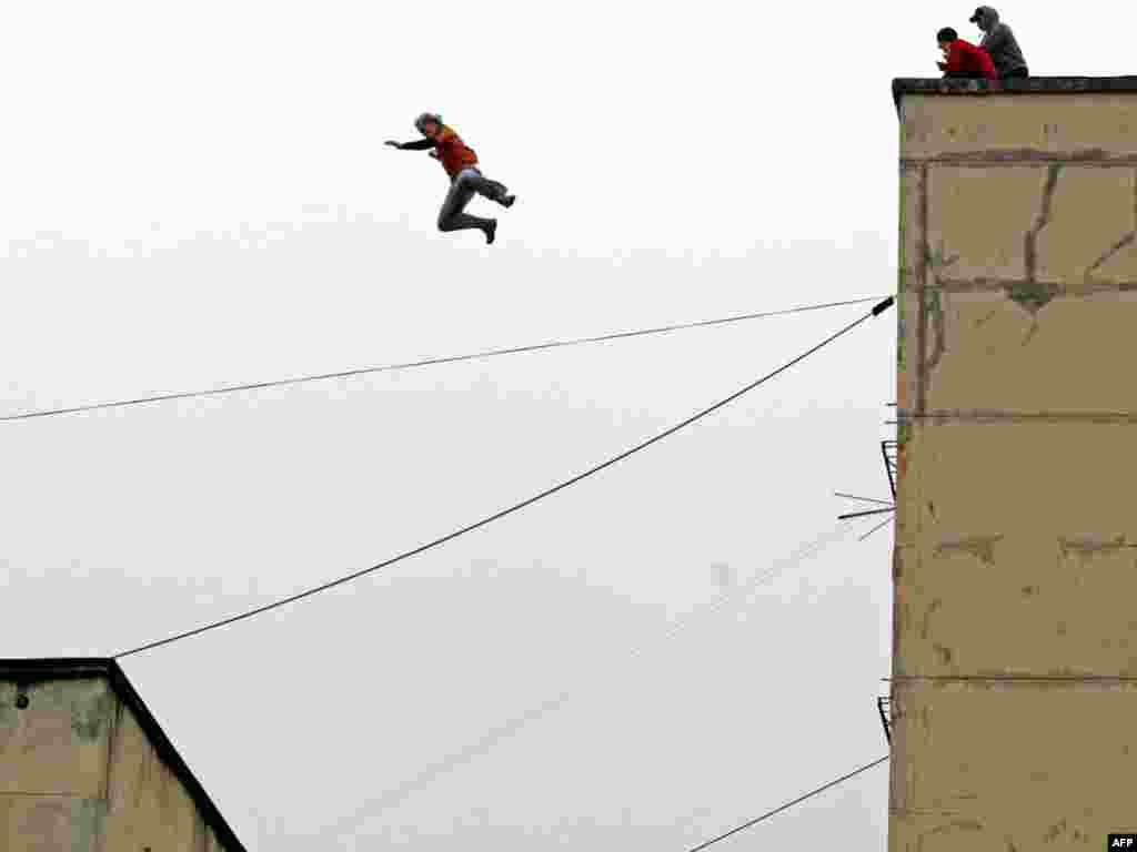 Росія. Ентузіаст паркуру стрибає з восьмиповерхового будинку на п'ятиповерховий у Санкт-Петербурзі - Паркур - спортивна дисципліна, що являє собою швидке подолання перешкод. Паркур був заснований у Франції Давідом Беллем і Себастьяном Фука. Поєднує в собі особливу філософію (світосприймання), гімнастику, легку атлетику, бойові мистецтва і білдерінг (лазіння по стінах). Люди, які займаються паркуром, називаються трейсерами.Photo by Kirill Kudryavtsev for Topshots/AFP