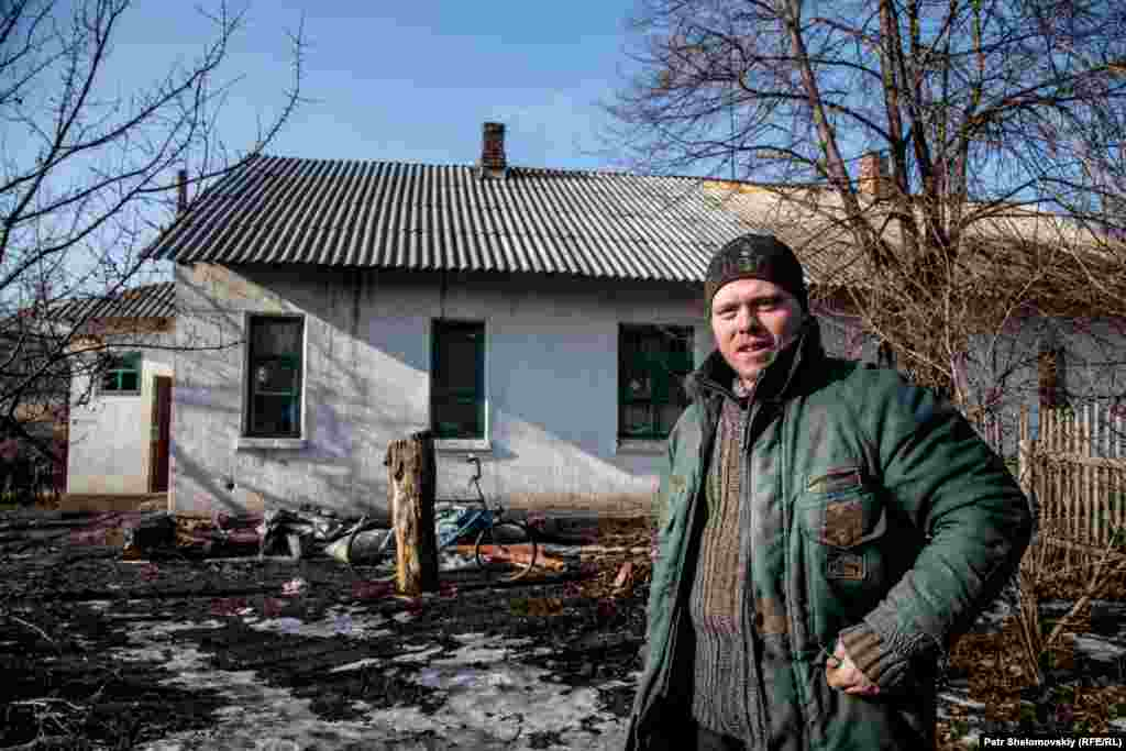 Ivan stands in front of his family's house in the Petrovskiy district of Donetsk. He is unemployed, and the only family income comes from welfare payments for his three children.