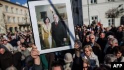 Варшава. Участники демонстрации в память погибших президента Леха Качиньского и его супруги держат их портрет в траурной рамке