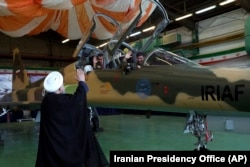 Iranian President Hassan Rohani waves to the pilots of a fighter jet before an inauguration ceremony of the aircraft on August 21.