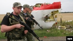 Armed pro-Russia militants walk next to the wreckage of Flight MH17 in eastern Ukraine near Donetsk on July 18, 2014.