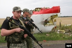 Armed pro-Russia militants walk past wreckage from MH17 near Donetsk on July 18, 2014.