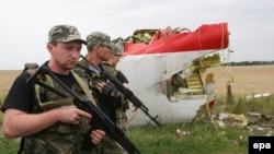 Armed Russia-backed militants walk past wreckage of Malaysia Airlines flight MH17 debris in July 2014.