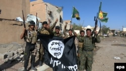 Iraqi soldiers and Shi'ite volunteers hold a flag belonging to the Islamic State extremist group after they regained control of Tikrit, April 1, 2015.