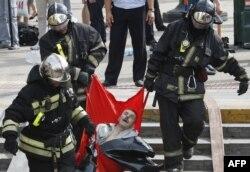 Спасатели выносят пострадавшего в аварии поезда метро