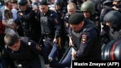 Полиция қызметкерлері наразылық шеруіне қатысқан адамды ұстап әкетіп барады (Көрнекі сурет).