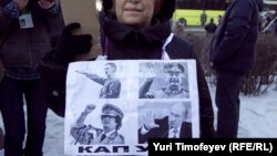 "A woman holds a sign featuring Adolf Hitler, Josef Stalin, Muammar Qaddafi, and Vladimir Putin, and below it says ""Kaput!"""