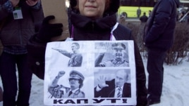 "A woman holds a sign featuring Adolf Hitler, Josef Stalin, Muammar Qaddafi, and Vladimir Putin, and below it says ""Kaput!"""