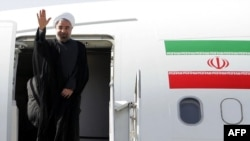 President Hassan Rohani waves before entering an airplane upon his departure to the United States to attend the UN General Assembly, at Tehran's Mehrabad Airport, September 23, 2013
