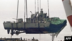 A floating crane lifts the stern of the South Korean warship to place it on a barge during recovery operations in mid-April, nearly three weeks after it sank.
