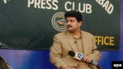 FILE: Hamid Mir recoded his television show outside the Islamabad Press Club to protest a ban by military dictator Pervez Musharraf in 2007.