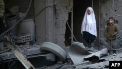 Siriýaly çagalar howa hüjümlerinden soňky halas ediş çärelere syn edýärler, Douma şäheri, 10-njy ýanwar, 2016.