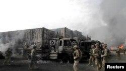 Военнослужащие НАТО рядом с горящими грузовиками после нападения боевиков.
