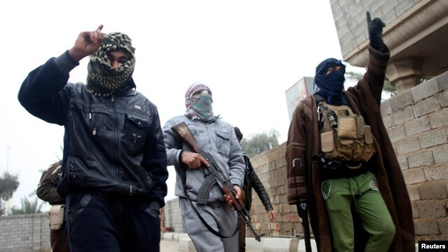 Islamist fighters walk the streets of Fallujah on January 3, after taking control of much of the western Iraqi city.