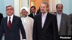 Armenian President Serzh Sarkisian (left) meets with Iran's parliament speaker, Ali Larijani, in Yerevan on October 9.