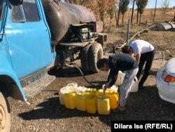 Жители Акжара набирают воду из «общего» колодца.
