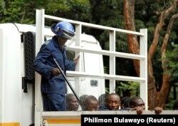 Наразылық кезінде ұсталғандардың жанында тұрған полиция. Хараре, 16 қаңтар 2019 жыл.
