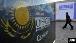 Прохожие рядом с билбордом о саммите Организации по безопасности и сотрудничеству в Европе (ОБСЕ). Астана, декабрь 2010 года.