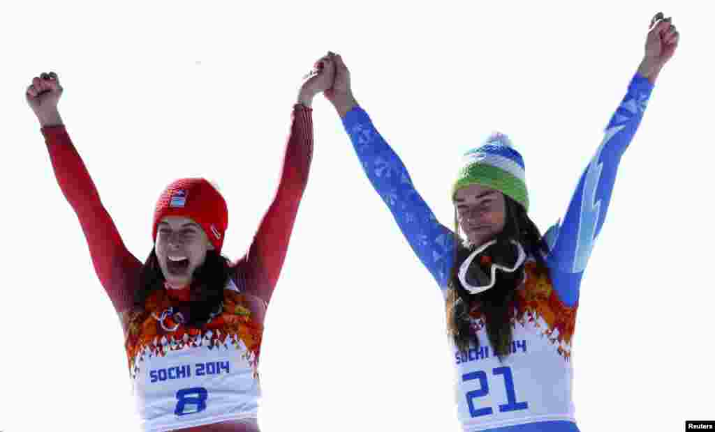 Joint winners Dominique Gisin of Switzerland (left) and Tina Maze of Slovenia celebrate on the podium after the women's alpine-skiing downhill event during the flower ceremony.