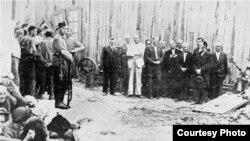 Lideri ai comunității evreieşti din oraşul Bălți înainte de a fi executați la 15 iulie 1941. În stânga, în picioare, soldați germani (foto: Matatias Carp, Cartea Neagră - Bucureşti, 1947, Vol. 3 (Transnistria).