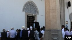 Мужчины во время пятничной молитвы у мечети в Приштине.