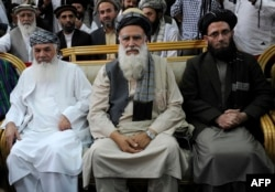 Former Islamist warlord, Abdul Rasul Sayyaf (C) sits with his two vice-presidential candidates, Mohammad Ismail Khan (L) and Abdul Wahab Erfan (file photo)
