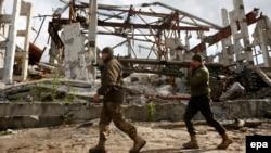 Украинские солдаты идут рядом с поврежденным зданием Бутовской угольной шахты. Май 2017 года