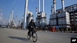 An Iranian oil worker rides his bicycle at a Tehran oil refinery. (file photo)