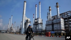 FILE - In this Dec. 22, 2014 file photo, an Iranian oil worker rides his bicycle at the Tehran oil refinery