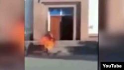 """На кадре из видеоролика — горящий Ерлан Бектибаев вбегает в здание филиала партии """"Нур Отан"""" в Таразе. 24 октября 2015 года."""