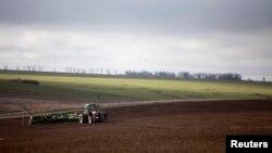 Көктемде далада жер жыртып жүрген трактор. (Көрнекі сурет.)