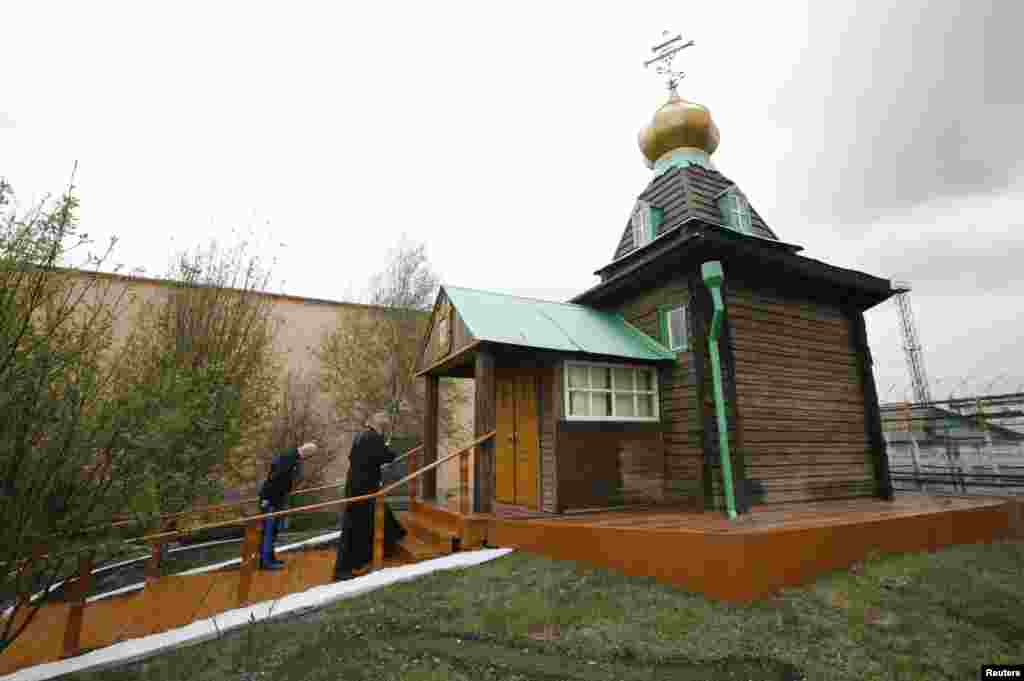 An Orthodox priest and an inmate stand in front of an Orthodox church on the prison grounds.