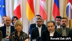 The European Union's political director Helga Schmid and Iranian deputy Foreign Minister Abbas Araghchi, from left, wait for a bilateral meeting as part of the closed-door nuclear talks with Iran at a hotel in Vienna, July 28, 2019