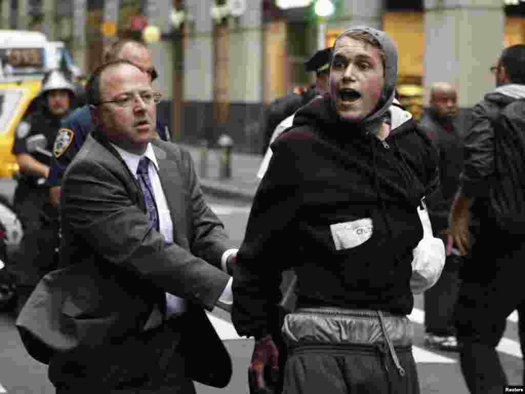 """Oktyabrın 14-də New York polisi """"Wall Street-i tutaq"""" şüarı ilə etiraz askiyası keçirənlərdən birini həbs edir. (Foto: Lucas Jackson/Reuters)"""