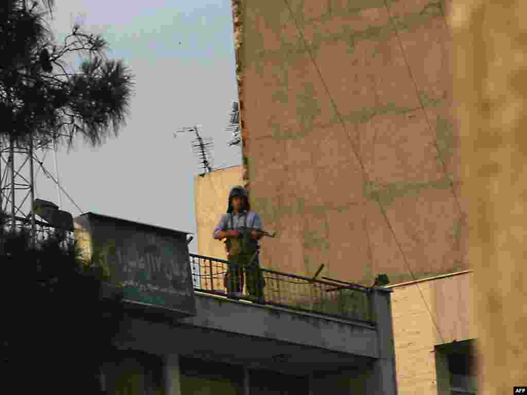 A gunman monitors the demonstrations from a rooftop.