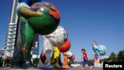 Астанадағы EXPO-2017 көрмесіне қатысушы елдерді бейнелейтін мүсіндердің қасынан өтіп бара жатқан бала. 29 қыркүйек 2016 жыл.