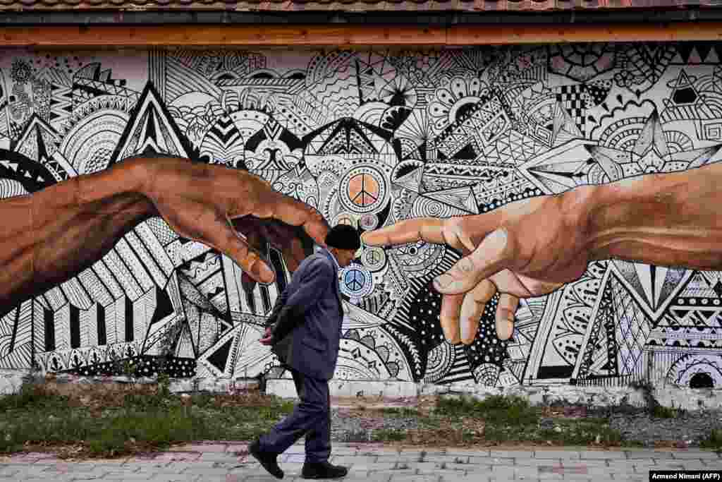 A pedestrian walks past a mural painted on the wall of a house in the town of Ferizaj, Kosovo. (AFP/Armend Nimani)