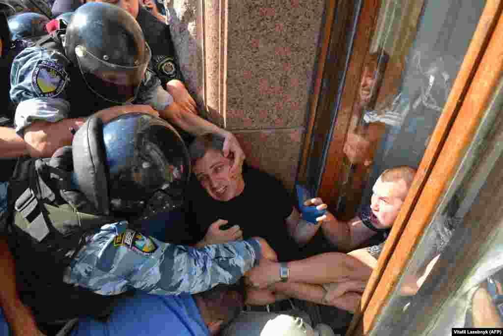 Riot police grapple with an opposition deputy trying to enter the Kyiv city council through a window in August 2013.