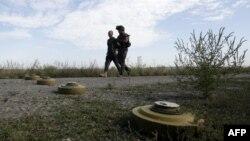 Військові проходять повз протитанкові міни, встановлені на позиціях українських сил в Луганській області, серпень 2015 року