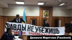Сотта прокурор сотқа негіз болған баннерді ұстап тұр. Алматы, 22 сәуір 2019 жыл.