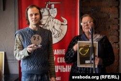 Сябры журы Віктар Жыбуль і Ганна Запартыка трымаюць узнагароды за другое месца