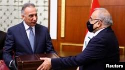 Former Iraqi Prime Minister Adel Abdul Mahdi (R) hands over to new Prime Minister Mustafa al-Kadhimi in Baghdad, Iraq, May 7, 2020